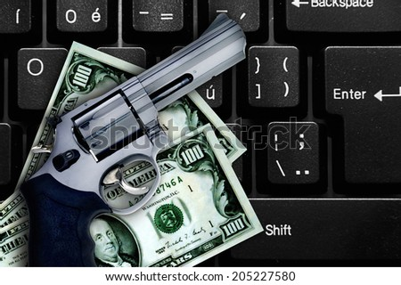 gun and dollars on a laptop, internet crime concept