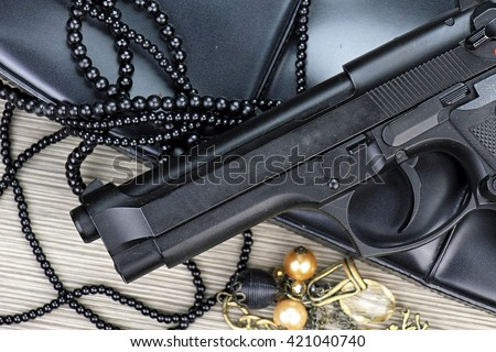 Gun and purse, Woman bag with gun, Woman's clutch purse with gun and accessories, Handgun and accessories falling from a woman's purse. - stock photo