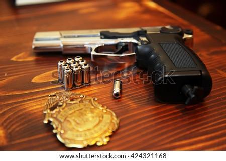 Gun, bullets and police badge - stock photo