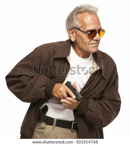 Gun Concealed Carry | PERSONAL DEFENSE | A mature man legally carries a firearm in a holster on his hip, concealed under a jacket. - stock photo