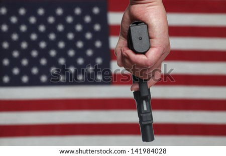 Gun Control USA Style/Hand holding automatic pistol over slightly blurred background of US Flag - stock photo