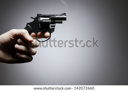 Gun crime concept of hand pistol on grey background - stock photo