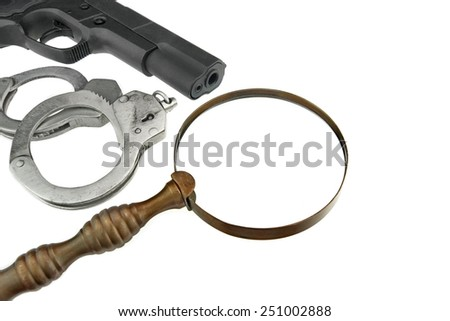 Gun, Handcuffs and Magnifying Glass Isolated on White Background - stock photo