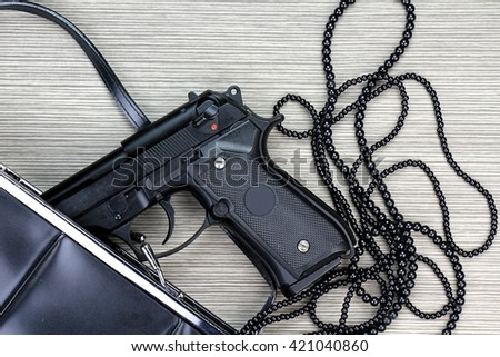 Gun in a purse, Woman bag with gun hidden, Woman's clutch purse with gun and accessories, Handgun and accessories falling from a woman's purse. - stock photo