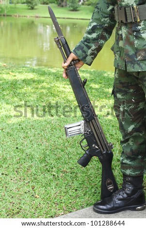 Gun in hand of soldier - stock photo