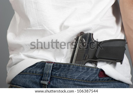 Gun inserted by the waist of jeans at the young man