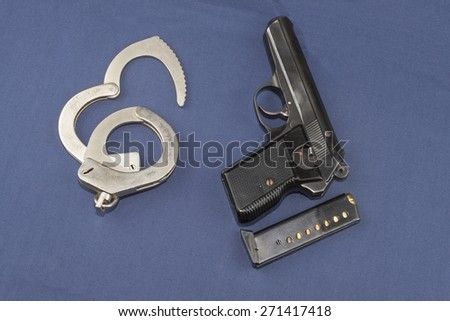 gun, magazine and police handcuffs lying on the table - stock photo