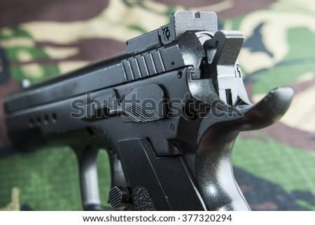 gun on camouflage background - stock photo