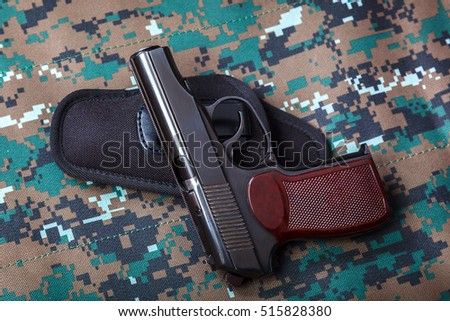 Gun on camouflage background. Weapons. Tactical gun and holster.