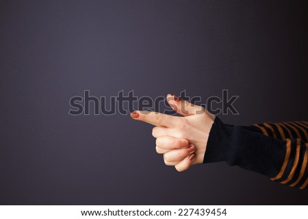 Gun shaped woman hand with empty space - stock photo