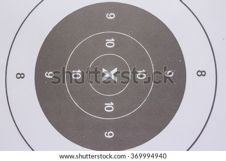 Gun shooting target with bullet hole.