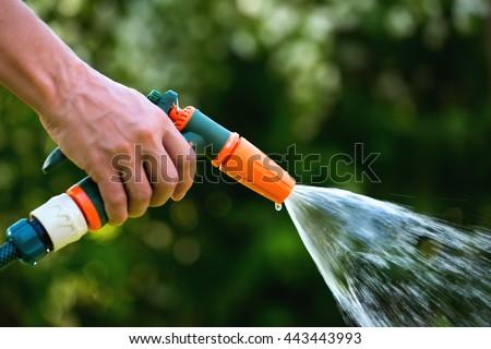 Gun Water Hose Nozzle Sprayer. Woman Hand Holding Hose Sprayer Head  Watering Garden. Shallow