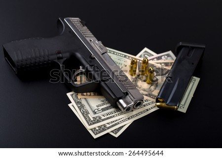 gun with bullet on US dollar banknotes, crime or corruption concept on black backgroud - stock photo