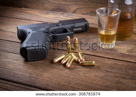 Gun with bullets and whiskey on the wooden floor - stock photo