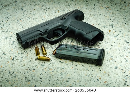Gun with magazine and ammo on floor - stock photo