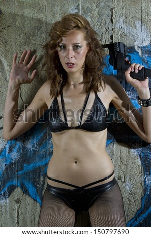 Gun woman standing at the wall in surrendering position with hands up - stock photo