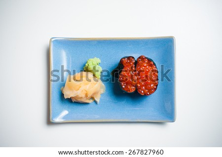 Gunkan, sushi on blue plate with ginger and wasabi, white background - stock photo