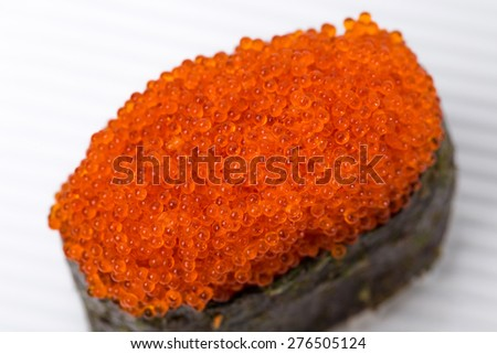 Gunkan sushi stuffed with red tobiko caviar. Macro. Located on ceramic plate. Can be used as a whole background.