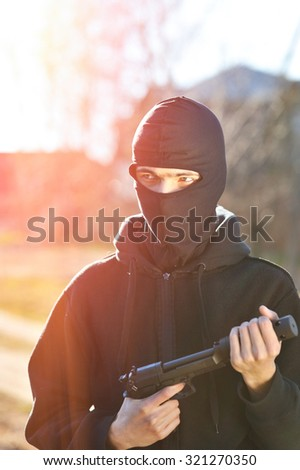 Gunman in black mask holding gun with silencer - stock photo