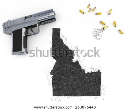 Gunpowder forming the shape of Idaho and a handgun.(series) - stock photo