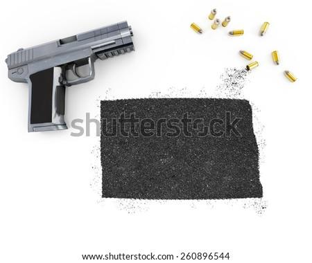 Gunpowder forming the shape of North Dakota and a handgun.(series) - stock photo