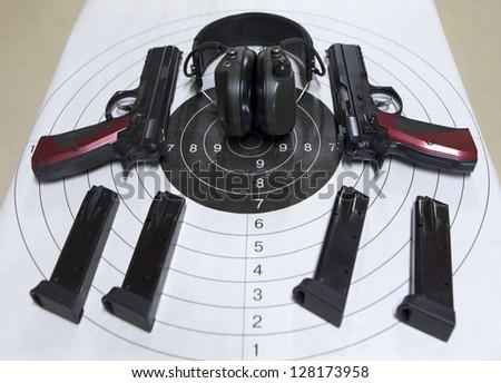 Guns cartridges target headset in a shooting range - stock photo