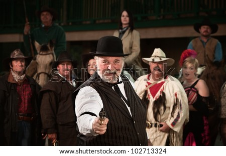 Gunshooter with gang in old American west theme - stock photo
