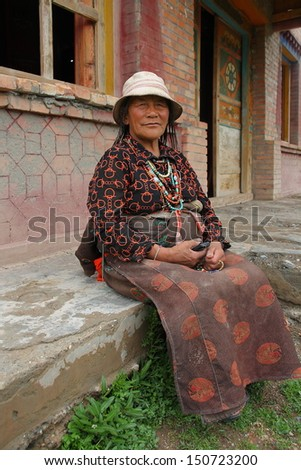 GUOLUO, CHINA - JULY 27: Unidentified old woman sit in a Tibetan Buddhism Temple on the Tibetan plateau, Tibetan people spend a lot of time on Buddhism, July 27, 2013, Guoluo, Qinghai, China