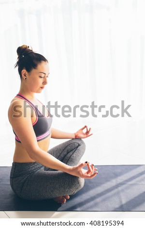 Guptasana. Beautiful yoga woman practice in a training hall background. Yoga concept. - stock photo