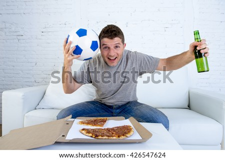 guy alone at home holding ball and beer bottle watching football game on television sitting on living room sofa couch with pizza box celebrating  goal or victory gesturing crazy - stock photo
