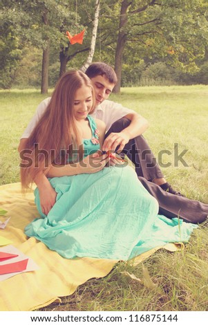 guy and girl doing origami at a picnic in the park, tinted - stock photo