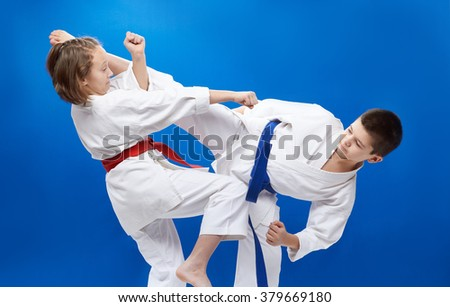 Guy and girl in kimono perform karate techniques - stock photo