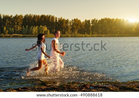 Guy and girl in white clothes runs on the river