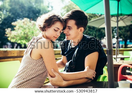 guy and the girl sitting in a cafe outside