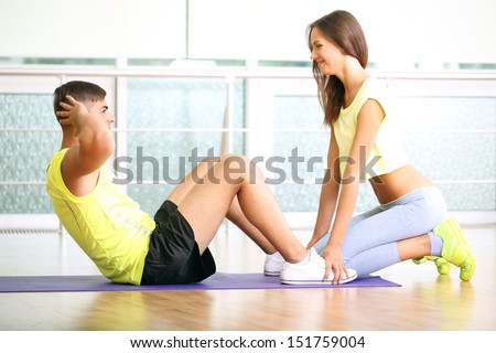 Guy and trainer engaged in fitness room - stock photo