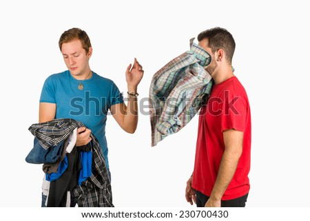 Guy being pretty choosy and dainty about  clothes - stock photo