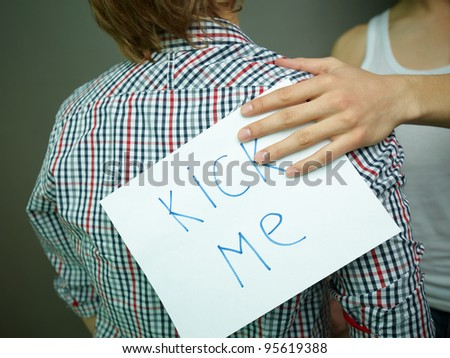 Guy being unaware of a �Kick me� sign attached to his back - stock photo