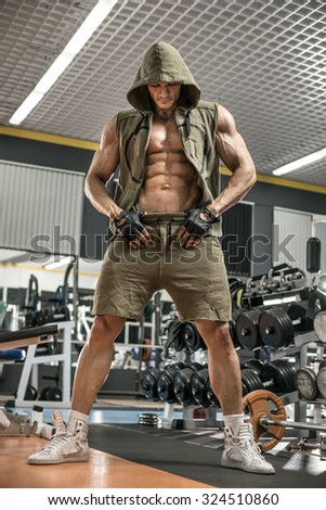 guy bodybuilder stand in gym, vertical photo - stock photo