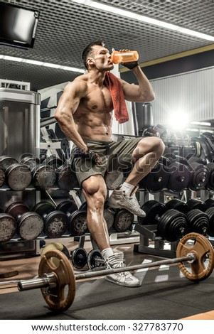 guy bodybuilder tired sit in gym and drink sportive nutrition - protein of shaker , vertical photo - stock photo