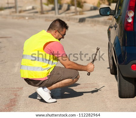 Guy completely unable to fix anything on his car - stock photo