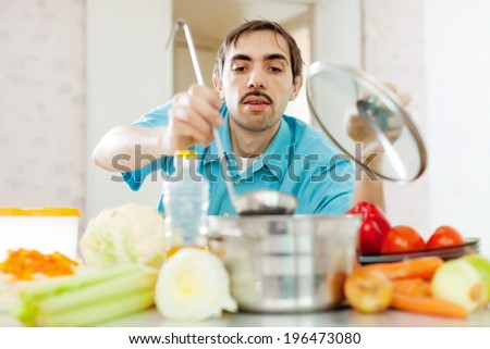 guy cooking vegetarian lunch at kitchen - stock photo