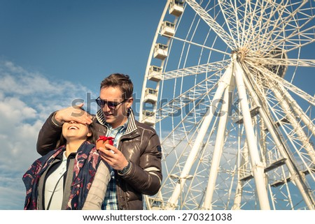 Guy covering eyes to his girlfriend and giving her a gift. Happy and smiling girl when the boyfriend surprised her with a present. Couple in love standing with ferris wheel in background. - stock photo