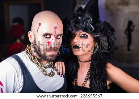 Guy dressed as pirate and woman dressed as witch, shot pirate Halloween costume, witch Halloween costume, Halloween party in costumes, friends at masquerade party having fun