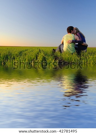 guy embraces girl on a spring field and kissing. Near the water - stock photo