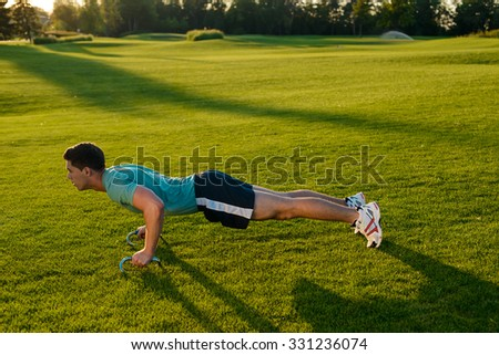 Guy engaged in sports in the park. Guy is wrung in her arms. Sports activities on the nature. Healthy lifestyle. - stock photo