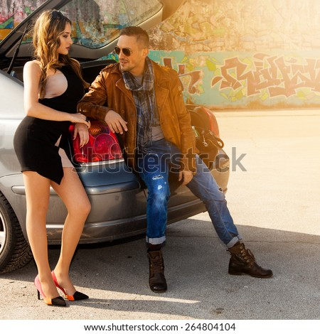 guy flirting with a girl sitting in a car trunk outdoors - stock photo