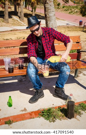 Guy getting heavily drunk on a park bench