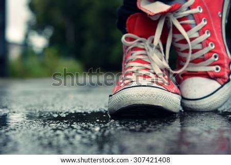 Guy goes in red sneakers on the street in the rain - stock photo