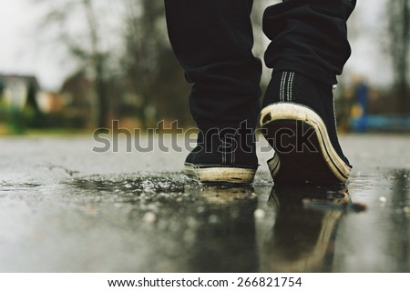 Guy goes in sneakers on the street in the rain - stock photo