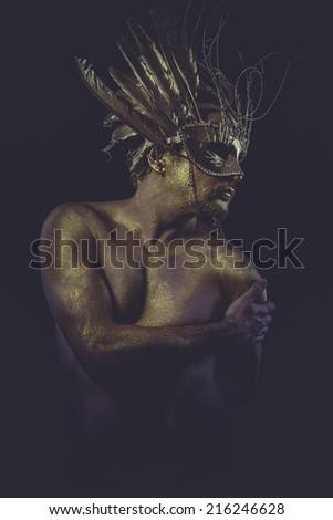 guy, golden bodypaint, man with gold helmet, ancient warrior deity - stock photo